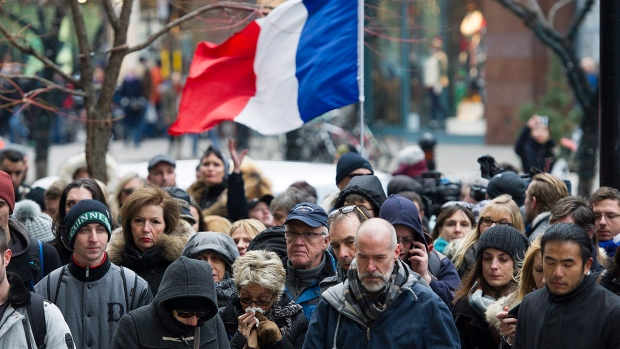 People attend a rally of solidarity outside the Consulate of France in Montreal, on Saturday, Nov. 14, 2015, to show their support to victims of the Paris attacks. THE CANADIAN PRESS/Graham Hughes