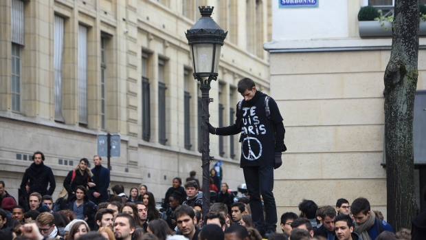 A man wearing a t-shirt reading 'I am Paris,' observes a minute' silence, outside the Sorbonne university, in Paris, Monday, Nov. 16, 2015. (AP / Thibault Camus)