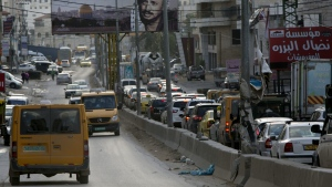 In this Tuesday, Nov. 10, 2015 photo, Palestinians drive near the Qalandia checkpoint between Jerusalem and the West Bank city of Ramallah. (AP Photo/Majdi Mohammed)