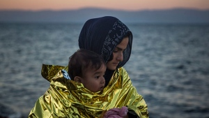A woman wearing a thermal blanket holds her child on a beach on the Greek island of Lesbos shortly after crossing the Aegean sea on a dinghy from the Turkey's coast with other refugees and migrants on Friday, Nov. 20, 2015. (AP Photo/Santi Palacios)