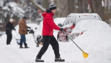 People clear snow from their cars in Montreal