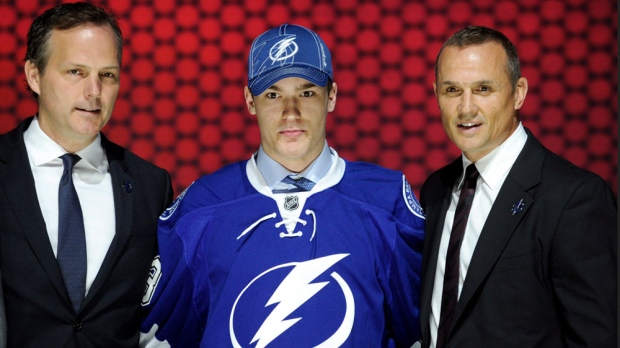 Jonathan Drouin stands with officials from the Tampa Bay Lightning after being chosen 3rd overall in the first round of the NHL hockey draft in Newark, N.J., Sunday, June 30, 2013. (AP / Bill Kostroun)