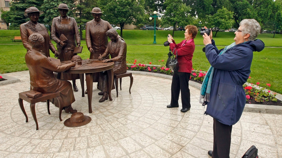 Wilma Wallcraft, right, and Darlene Hayward snap a few pictures of the Nellie McClung statue unveiled at the Manitoba Legislature in Winnipeg on Friday June 18, 2010. (Winnipeg Free Press-Ken Gigliotti / THE CANADIAN PRESS)