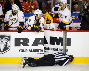Nashville Predators players look over the bench at linesman Don Henderson after he was hit by Calgary Flames' Dennis Wideman during second period NHL hockey action in Calgary, Alberta, Wednesday, Jan. 27, 2016. (Jeff McIntosh / The Canadian Press via AP)