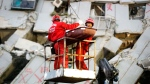Two emergency workers carry a victim recovered from a collapsed building in Tainan, Taiwan, Sunday, Feb. 7, 2016. (Wally Santana / AP)