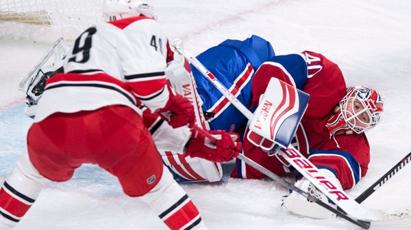 Montreal Canadiens goalie Ben Scrivens gloves the pick as Carolina Hurricanes' Victor Rask looks for a rebound during second period NHL hockey action Sunday, February 7, 2016 in Montreal. THE CANADIAN PRESS/Paul Chiasson
