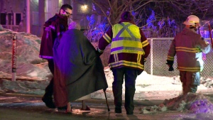 Firefighters assist an elderly lady after a fire broke out at a seniors' residence in Bois des Filion (CTV Montreal/Cosmo Santamaria)