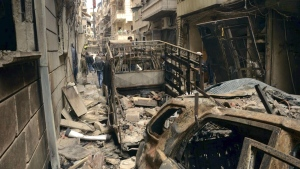 Syrians gather in a street that was hit by shelling, in the predominantly Christian and Armenian neighborhood of Suleimaniyeh, Aleppo, Syria on April 11, 2015. (SANA)