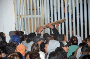 Relatives of inmates try to ram a piece of wood at police, who are standing on the other side of a gate, at the Topo Chico where a riot broke out around midnight, in Monterrey, Mexico, Thursday, Feb. 11, 2016. (AP Photo/Emilio Vazquez)