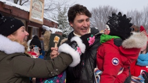Prime Minister Justin Trudeau, centre, holds his son Hadrian, right, as his wife Sophie Gregoire-Trudeau feeds him maple taffy, Saturday, February 13, 2016 at the Quebec Winter Carnival in Quebec City. THE CANADIAN PRESS/Jacques Boissinot