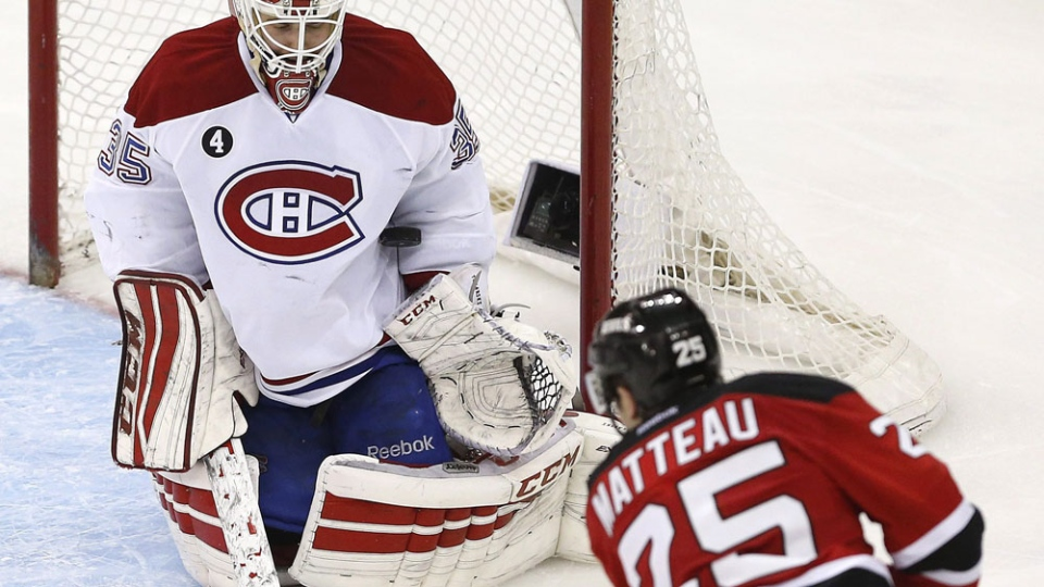 Montreal Canadiens goalie Dustin Tokarski (35) blocks as shot by New Jersey Stefan Matteau (25) during the third period of an NHL hockey game, Friday, April 3, 2015, in Newark, N.J. The Devils won 3-2 in a shootout. (AP Photo/Julio Cortez)