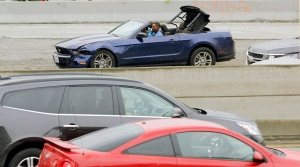 Two people in a convertible Mustang speed down the busy Harbor Freeway (Interstate 110) in downtown Los Angeles as they are pursued in a chase on rainy Southern California streets and highways, Thursday, April 7, 2016. (AP Photo/Reed Saxon)
