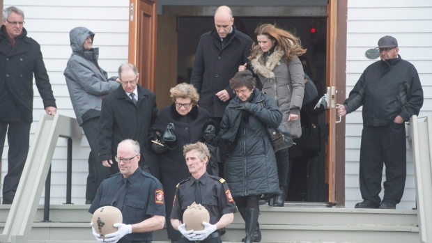 Jean Lapierre's mother Lucie Cormier is helped leaving the church by her surviving daughter Laure and an unidentified man and followed by Jean Lapierre's daughter Marie-Anne with her partner Mathieu Belhumeur following funeral services for the former Liberal cabinet minister and five of his relatives Friday, April 8, 2016 in Bassin, Que. THE CANADIAN PRESS/Paul Chiasson
