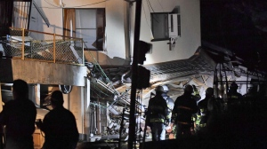 Firefighters search for trapped residents at a collapsed house in Mashiki, near Kumamoto city, southern Japan, after the earthquake early Friday, April 15, 2016. (Kyodo News via AP)