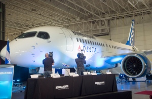Media take pictures of Bombardier's CS100 aircraft
