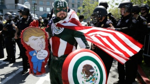 Erik Lopez, dressed as 'Captain Mexico', stands in front of police officers while protesting Republican presidential candidate Donald Trump outside of the Hyatt Regency hotel during the California Republican Party 2016 Convention in Burlingame, Calif., Friday, April 29, 2016 (AP / Eric Risberg).