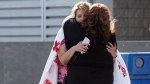 Evacuees from the wildfires in and around Fort McMurray hug at the evacuation centre at the Edmonton Expo Centre in Edmonton Alta, on May 4, 2016. (Codie McLachlan / THE CANADIAN PRESS)