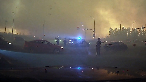 Police direct traffic in the Fort McMurray evacuation (taken from Youtube)