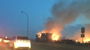 Cars drive by a burning structure on the west site of Hwy 63 southbound where a Humpty's family restaurant used stand in Fort McMurray, Alta. Tuesday, May 3, 2016. (Stephan Shatara for CTV News)