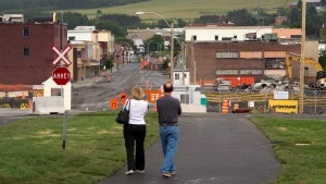 A couple looks at the downtown core Friday, July 4, 2014 in Lac-Megantic, Que. The one year anniversary of the train derailment and fire that left 47 people dead will be observed July 6, 2014. (THE CANADIAN PRESS / Ryan Remiorz)