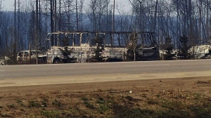In this Thursday, May 5, 2016 photo provided by the Royal Canadian Mounted Police Alberta, the charred remains of a bus sit on the side of a road in Fort McMurray, Alberta.(Royal Canadian Mounted Police Alberta via AP)
