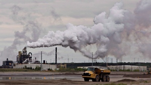 A dump truck works near the Syncrude oil sands extraction facility near the city of Fort McMurray, Alta., on June 1, 2014. (THE CANADIAN PRESS / Jason Franson)