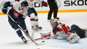 Slovakia's Martin Reway, left, attacks the net of Keith Kinkaid of the U.S. during the Hockey World Championships Group B match in St.Petersburg, Russia, Tuesday, May 17, 2016. (AP Photo/Dmitri Lovetsky)