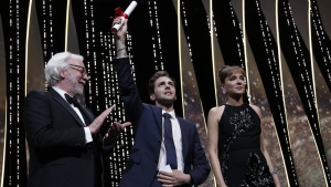 Director Xavier Dolan, centre, is awarded the Grand Prix award for the film It's only the end of the world, during the awards ceremony at the 69th international film festival, Cannes, southern France, Sunday, May 22, 2016. (AP Photo/Thibault Camus)