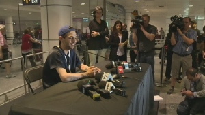 Xavier Dolan talks to reporters at Trudeau airport on May 23, 2016