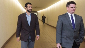 Omar Khadr, left, leaves court with his lawyer Nate Whitling, right, after a judge ruled to relax bail conditions in Edmonton on Sept. 18, 2015. (THE CANADIAN PRESS/Amber Bracken)