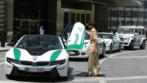 Dubai police Lt. Saif Sultan Rashed al-Shamsi, who oversees the tourist police's patrol section, pushes down one of the twin scissor doors of the $140,000 BMW i8 during a demonstration in Dubai, United Arab Emirate on Thursday May 19, 2016. (AP / Kamran Jebreili)
