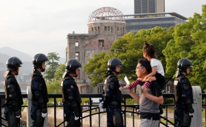 With the Atomic Bomb Dome as a backdrop, passersby move past riot police near Hiroshima Peace Memorial Museum in Hiroshima, southwestern Japan, Thursday, May 26, 2016. (AP / Shuji Kajiyama)