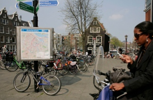 A Wednesday, April 23, 2008 photo from files showing a woman on a bicycle using her cellphone as she rides past a city map in Amsterdam, Netherlands. The Dutch government said Thursday, May 26, 2016 that it is considering banning the country's millions of cyclists from using their cellphones while riding, saying pedaling and phones are a dangerous mix. (AP Photo/Peter Dejong, File)
