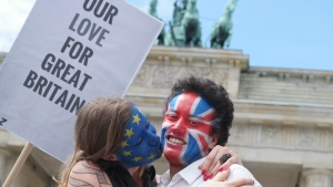 """A young couple with faces paint in European, left, and British colors, pose with a sign """"Our Love For Great Britain"""" during a Kiss Marathon event at Brandenburg Gate in Berlin, Germany, Sunday June 19, 2016 to support the ' Remain' voters in Britain's referendum. (Joerg Carstensen/dpa via AP)"""