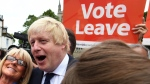 Advocate to exit Europe Boris Johnson poses for a selfie photo with voters during a whistle stop tour of the country on the final day of campaigning before Thursday's EU referendum vote, in Selby, north England, Wednesday June 22, 2016. (Andrew Parsons / PA via AP)
