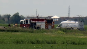 Firefighters and forensics crews at the scene of a deadly plane crash in St. Mathieu de Beloeil on June 24, 2016