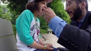 David Freiheit ties floss around his daughter's tooth