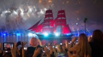 People watch a brig with scarlet sails on the Neva River during the Scarlet Sails festivities marking school graduation in St. Petersburg, Russia, early Sunday, June 26, 2016. This week graduation ceremonies and celebrations are held all over Russia as students of elementary and high schools and military academies finished their education. (AP Photo/Dmitri Lovetsky)