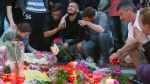 People mourn behind flower tributes near the Olympia shopping center where a shooting took place leaving nine people dead the day before, in Munich, Germany, Saturday, July 23, 2016. Police piecing together a profile of the gunman whose rampage at a Munich mall Friday left nine people dead described him Saturday as a lone, depression-plagued teenager. (Jens Meyer / AP)