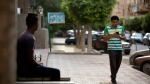 """In this Wednesday, July 20, 2016 photo, Egyptian dentist Mark Shehata, 24, uses the """"Pokemon Go,"""" mobile phone application while walking in Cairo, Egypt. (Amr Nabil/AP Photo)"""