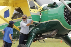 Harrison Ford opens the door on his plane for Jodie Gawthorp, of Westchester, Ill., who was selected to fly with Ford, at the Experimental Aircraft Associations AirVenture air show at Wittman Regional Airport in Oshkosh, Wis., Thursday, July 28, 2016. (Joe Sienkiewicz/The Oshkosh Northwestern via AP)