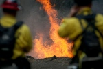 Cal Fire firefighters monitor a burning section of a wildfire on the Garzas Trail in the Santa Lucia Preserve above Carmel Valley, Calif., Thursday, July 28, 2016. (Nic Coury/Monterey County Weekly via AP)