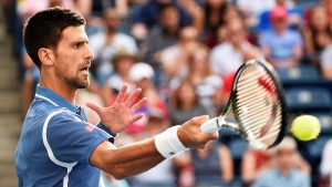 Novak Djokovic, of Serbia, returns the ball against Tomas Berdych, of the Czech Republic, during men's quarter-final Rogers Cup tennis action in Toronto on Friday, July 29, 2016. THE CANADIAN PRESS/Nathan Denette