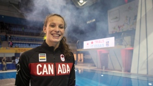 Penny Oleksiak walks off the podium after being introduced as a member of Canada's Olympic swim team during a ceremony following the final session of the Canadian Olympic swimming trials in Toronto on Sunday, April 10, 2016. (THE CANADIAN PRESS/Chris Young)