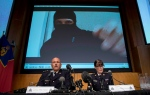 Video footage showing Aaron Driver is seen behind RCMP Deputy Commissioner Mike Cabana (left) and Assistant Commissioner Jennifer Strachan during a press conference for what the RCMP are calling a terrorism incident, in Strathroy, Ontario yesterday, on Thursday, Aug. 11, 2016 in Ottawa. (THE CANADIAN PRESS / Justin Tang)