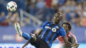 Montreal Impact defender Hassoun Camara kicks the ball in front of D.C. United forward Kennedy Igboananike during second half MLS action Wednesday, August 24, 2016 in Montreal. THE CANADIAN PRESS/Paul Chiasson