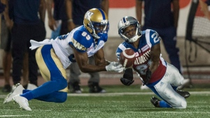 Winnipeg Blue Bombers wide receiver Clarence Denmark catches a pass ahead of Montreal Alouettes defensive back Jonathon Mincy during third quarter CFL football action Friday, August 26, 2016 in Montreal. THE CANADIAN PRESS/Paul Chiasson