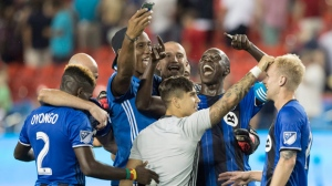 Montreal Impact teammates celebrate defeating Toronto FC following MLS soccer action in Toronto on Saturday, August 27, 2016. THE CANADIAN PRESS/Fred Thornhill