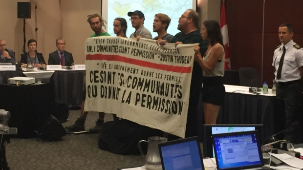 Protesters unfurl a banner denouncing the National Energy Board at public consultations into the Energy East pipeline on Monday morning. (Photo: CTV News/Wayne Toplosky)