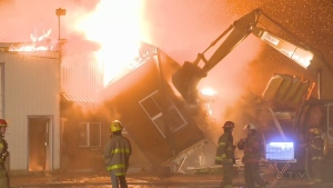 Firefighters watch as a backhoe is used to knock down buildings in Saint Alexis de Montcalm